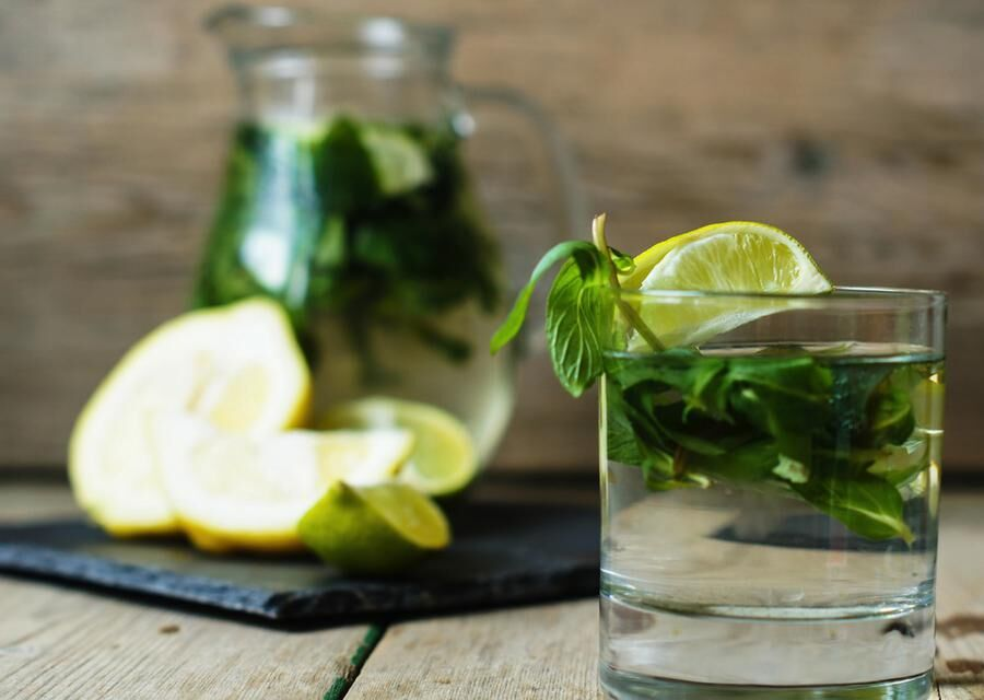 Lemonade with fresh mint, lime and lemon on the rustic kitchen