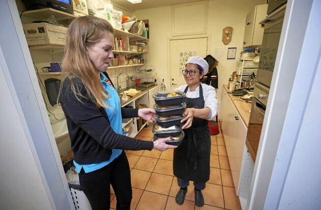 Lina hämtar en hög med nylagade matlådor, tillagade i lanthandelns kök av Kea Nitjaphod.