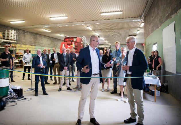 För att undkomma eventuellt dåligt väder klipptes bandet för laboratoriet inne i en närliggande maskinhall. LRF:s Palle Borgström med saxen i hand bredvid Christer Eliasson, ordförande i Hushållningssällskapet västra.