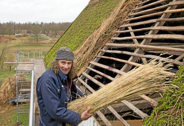Takläggaren och bonden Eje Arén bidrar med råghalm till sugrören.