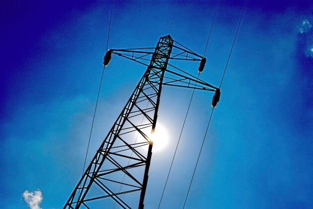 High voltage electricity pylon over blue sky and sun