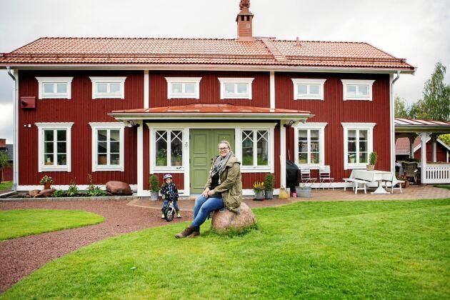 Helena Karlsson framför sitt egenritade drömhus med en gammal Hälsingegård som förlaga. Intill står 4-årige sonen Olle med sin cykel.