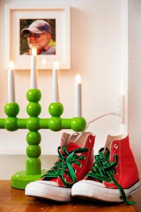 Adventsljusstaken friskt gröna färg ger fin kontrast åt den röda favoritskorna. På väggen ett foto av morfar.